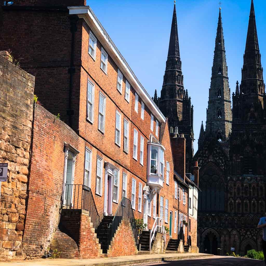 lichfield cathedral spires behind a row of houses