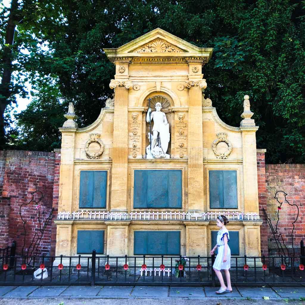 young girl in pretty dress walking past memorial in lichfields garden of remembrance