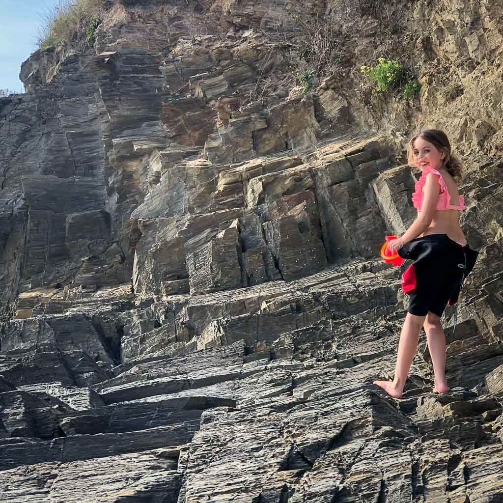 young girl in wetsuit climbing rocks at harlyn bay