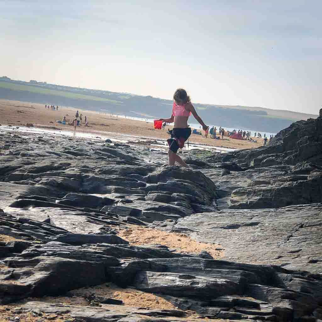 girl rock pooling at harlyn bay