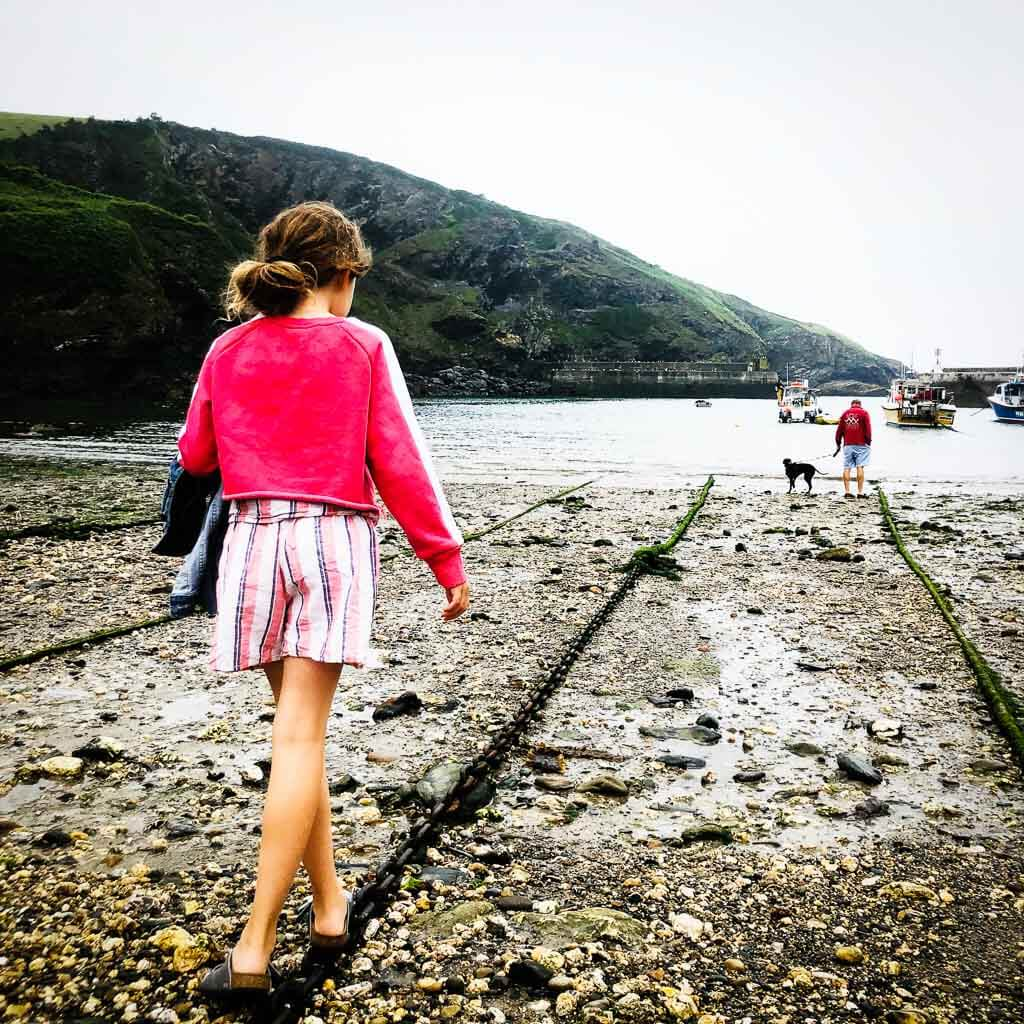 girl walking on anchor chain towards sea