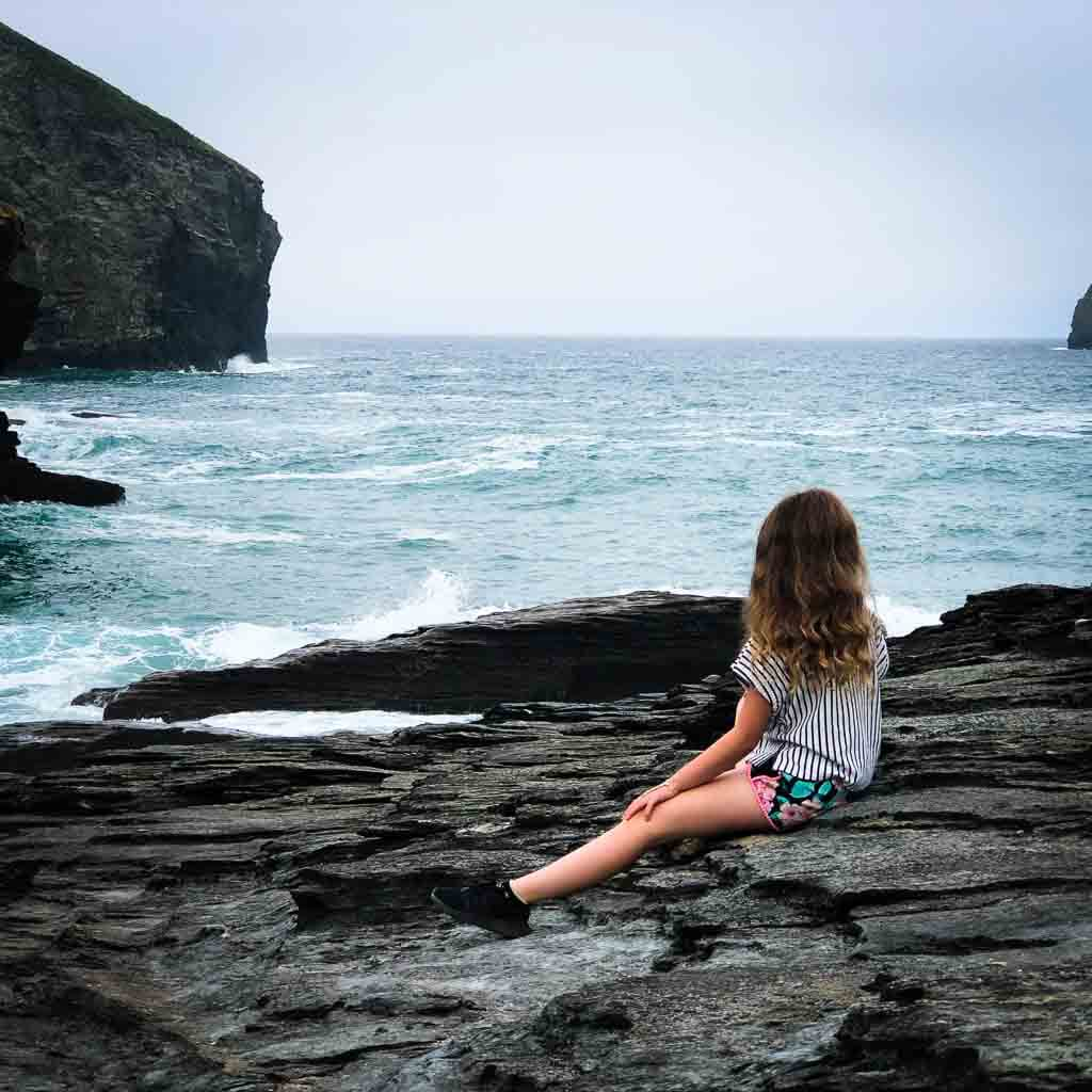 girl looking out to sea on black rocks