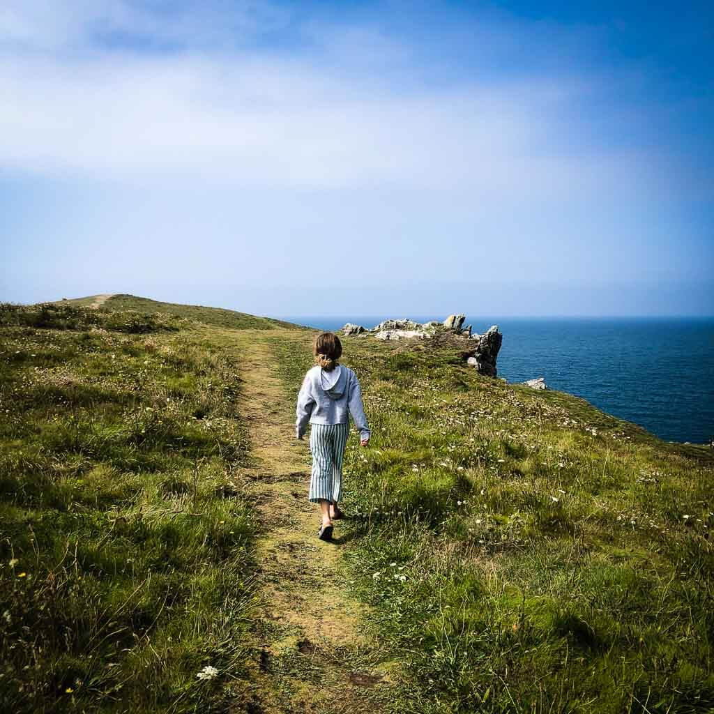 girl walking along the coastal path with sea views to her right