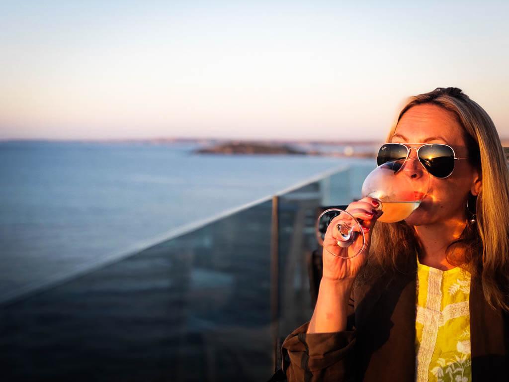 karen quinn drinking a glass of wine as the sun sets