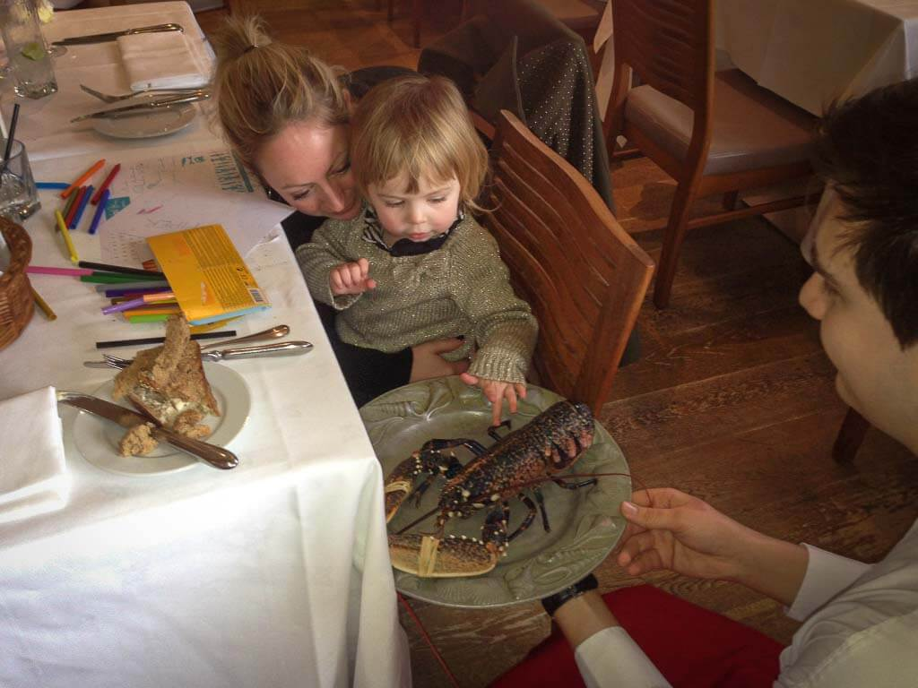 toddler touching a lobster at the seafood restaurant