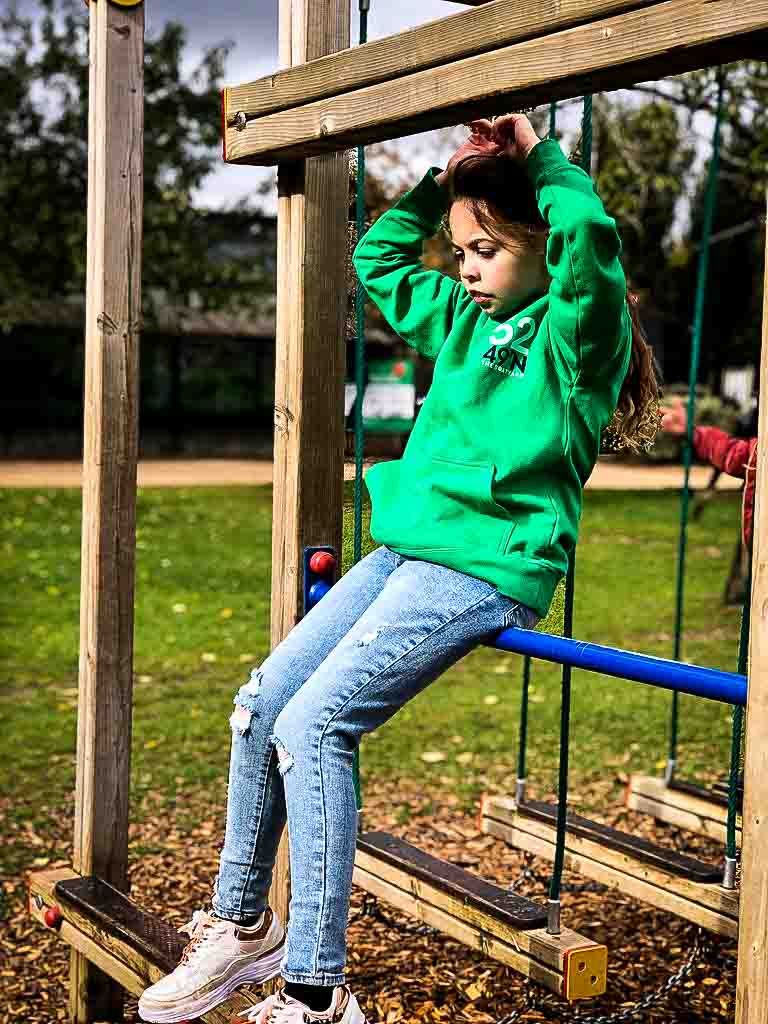 Young Girl Looking Pensive On Outdoor Play Equipment