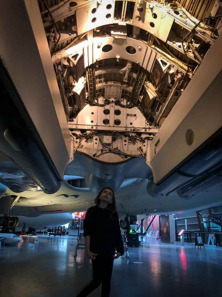 piper quinn looking up into a military aircraft suspended above