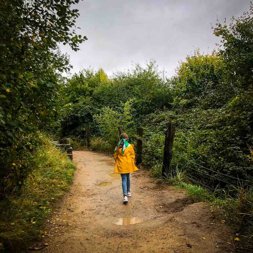 Girl In Yellow Jacket And Jeans Walking Down Muddy Path