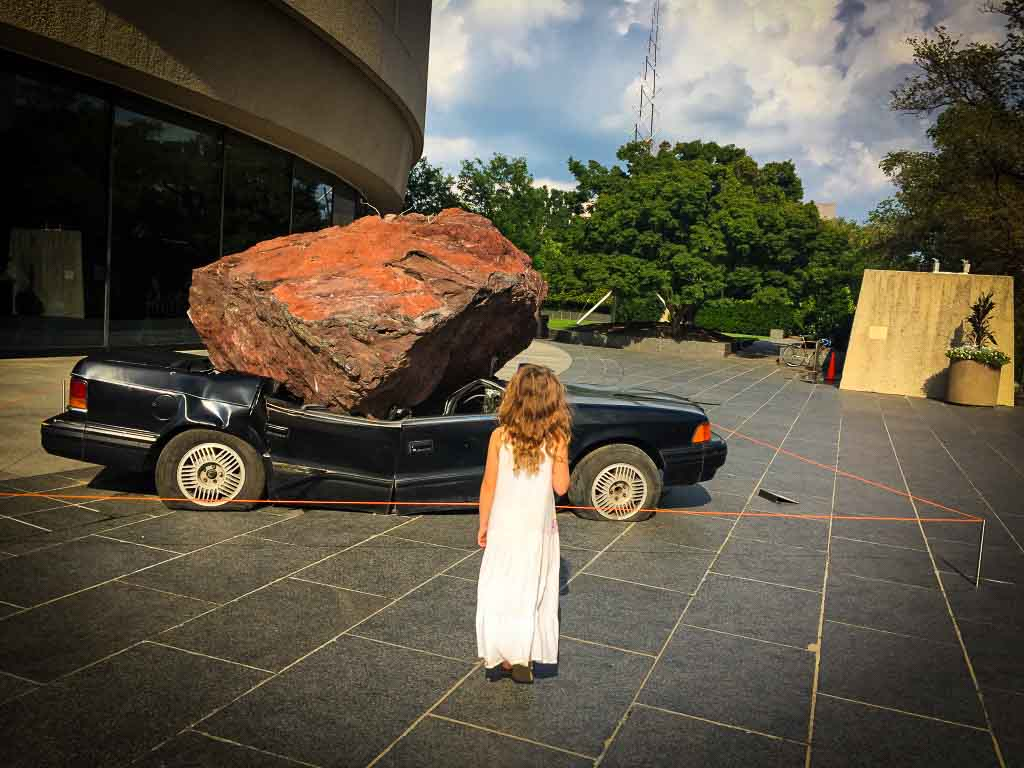 girl standing outside a car smashed by a boulder at the Hirshhorn gallery in washington