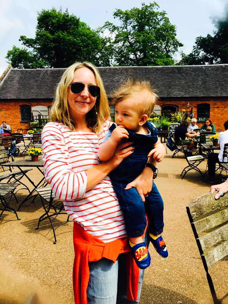 blonde lady in striped top holding toddler in blue dugarees at the barn restaurant at baddesley clinton