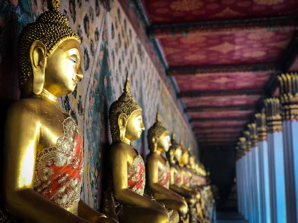 row of gold statues at a temple in bangkok