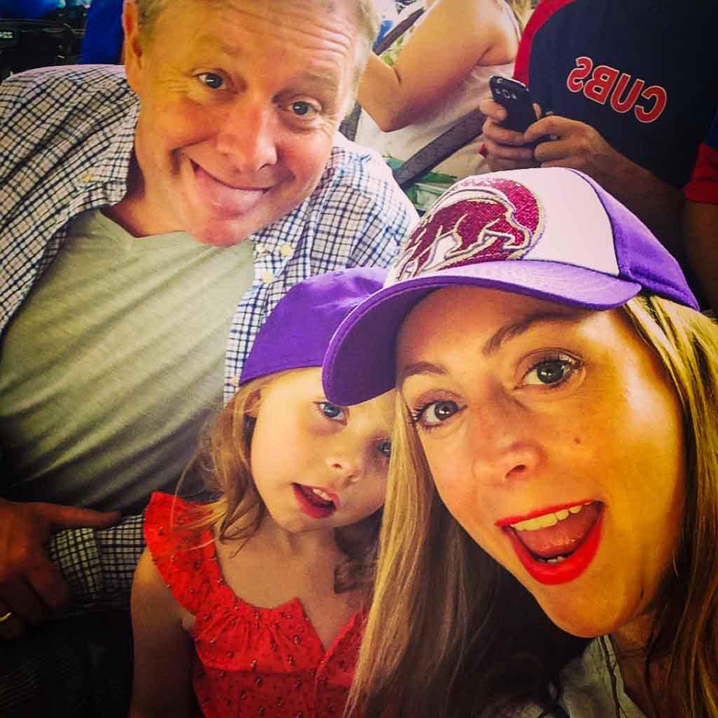 family of three at a ball game at wrigley field wearing cubs baseball caps