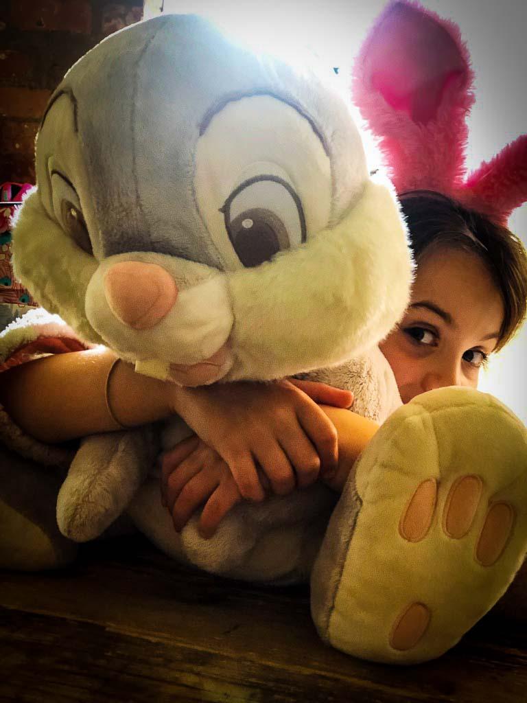 girl hugging huge stuffed easter bunny