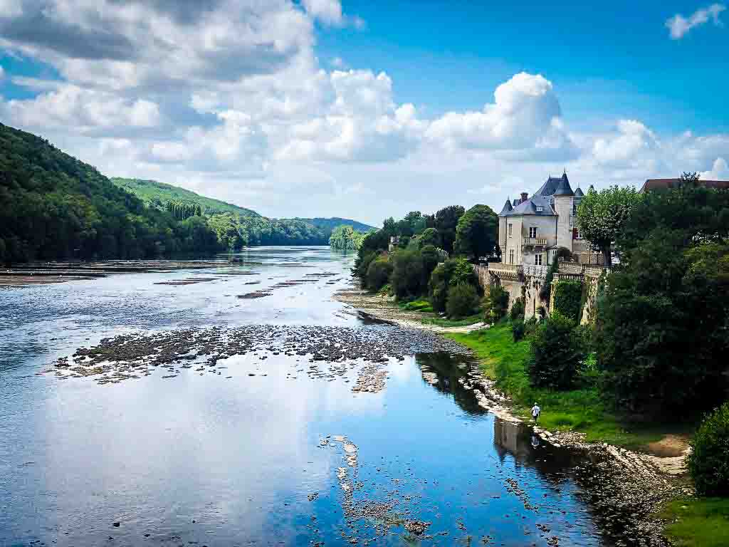 french chateau perched on the edge of a huge river