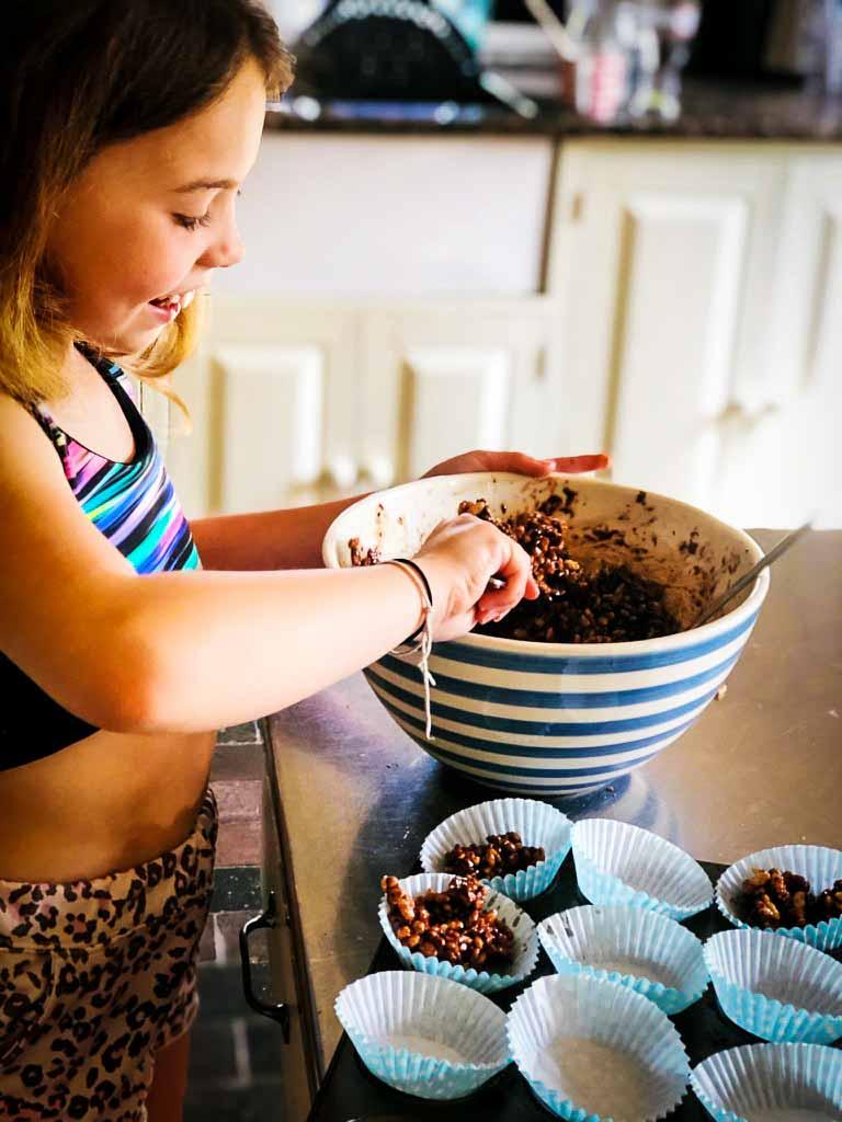 girl making a bowl of chocolate cornflake cakes