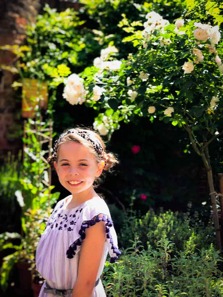 girl with seet buns miling in front of a pale pink rose bush in summer