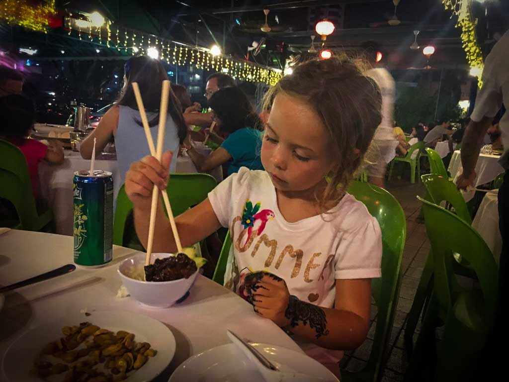 young girl holding chopsticks digging into a bowl of rice and ribs at a hawker centre in kuala lumpur