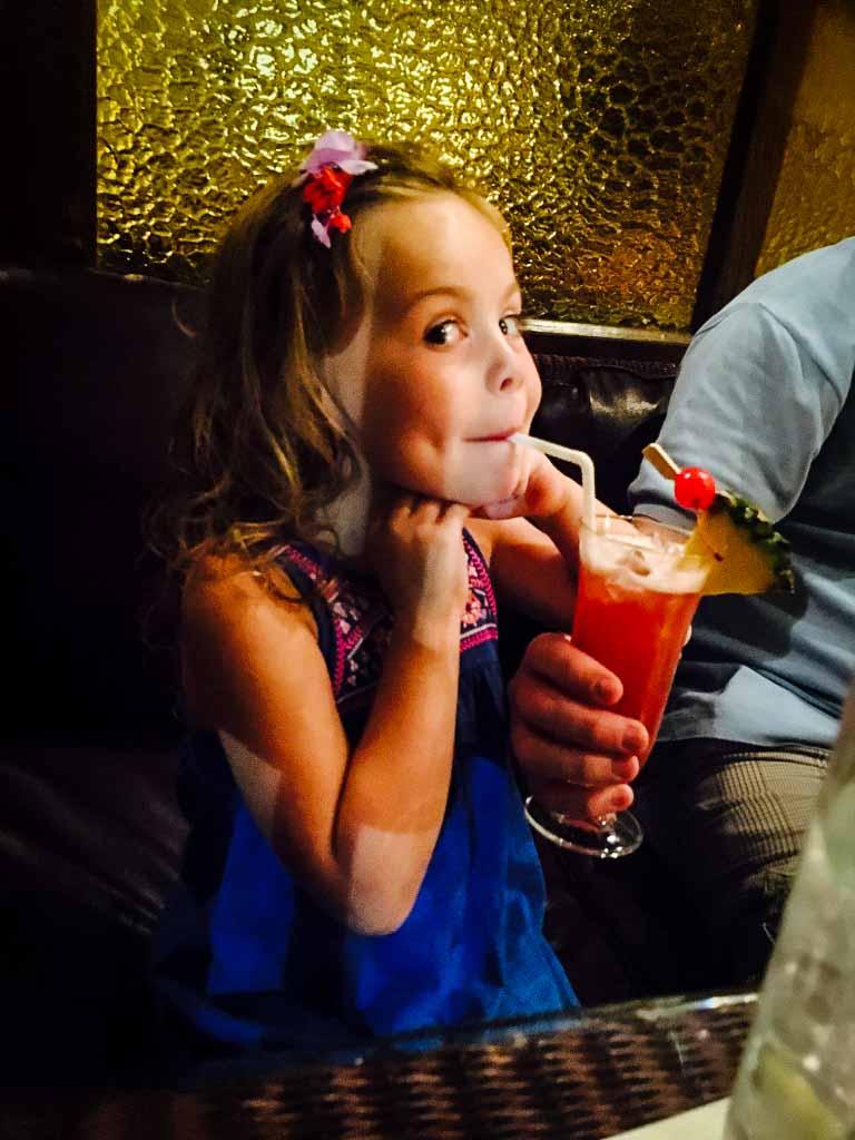 young girl drinking a virgin singapore sling at the long bar, raffles hotel, singapore