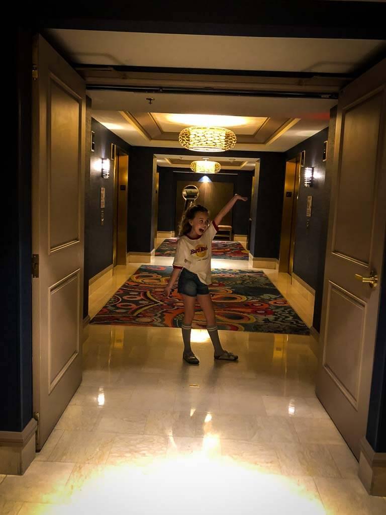 9 year old girl in denim shorts, long grey socks and tshirt striking a pose in a hotel corridor