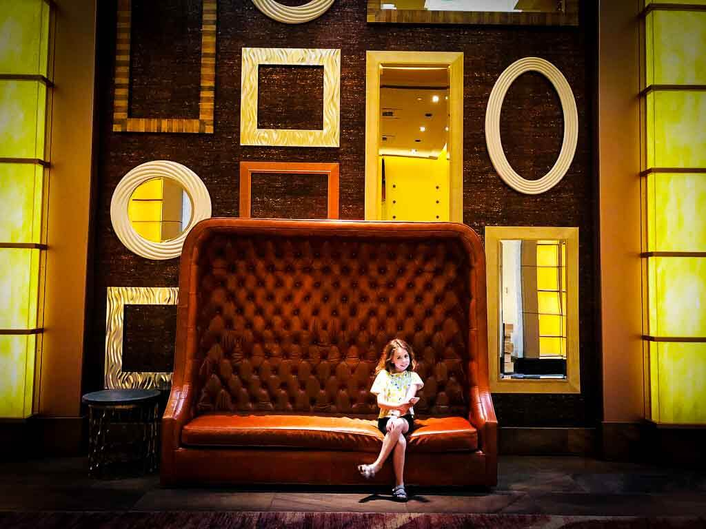 girl in tshirt and shorts sat on a high backed sofa with mirrors of all shapes on the wall behind
