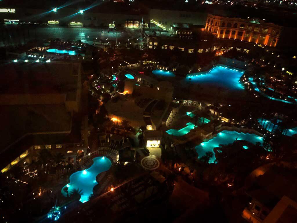 view of several pools at night time from mandalay bay hotel