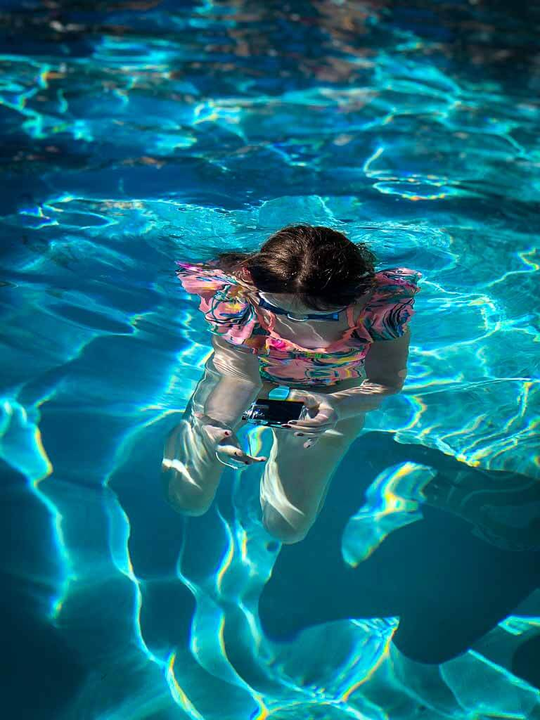 girl in pink swimsuit with goggles underwater taking a photo