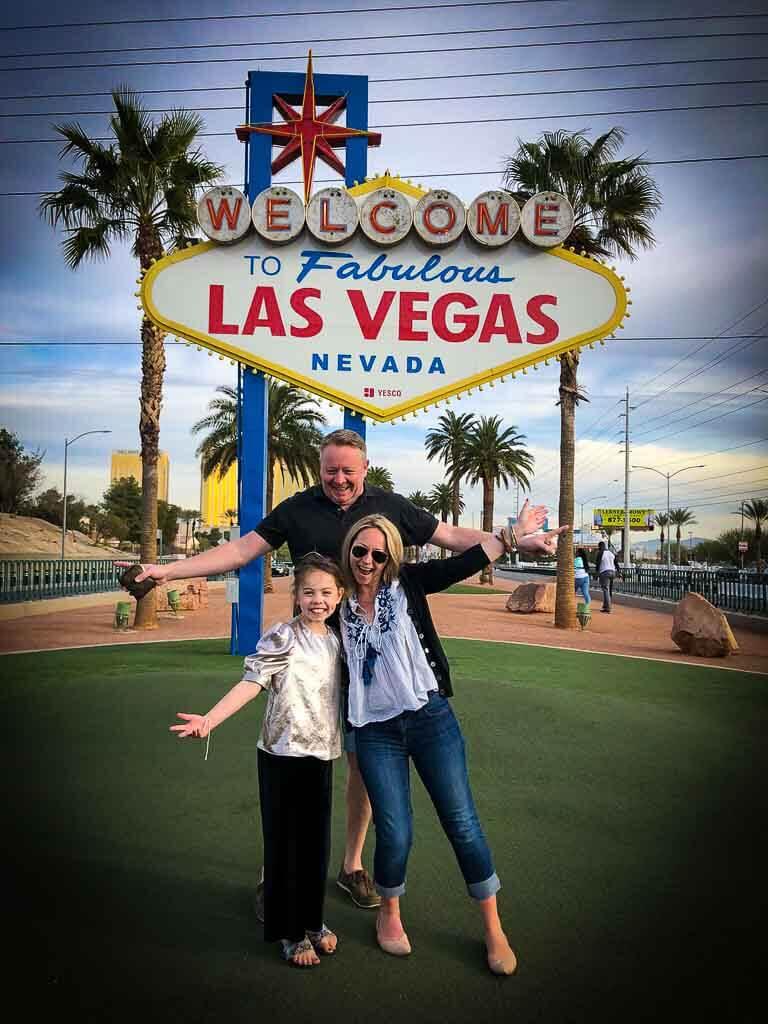 family of 3 posing outside the las vegas sign
