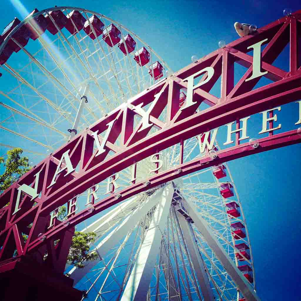 red navy pier sign with white writting and the big wheel behind
