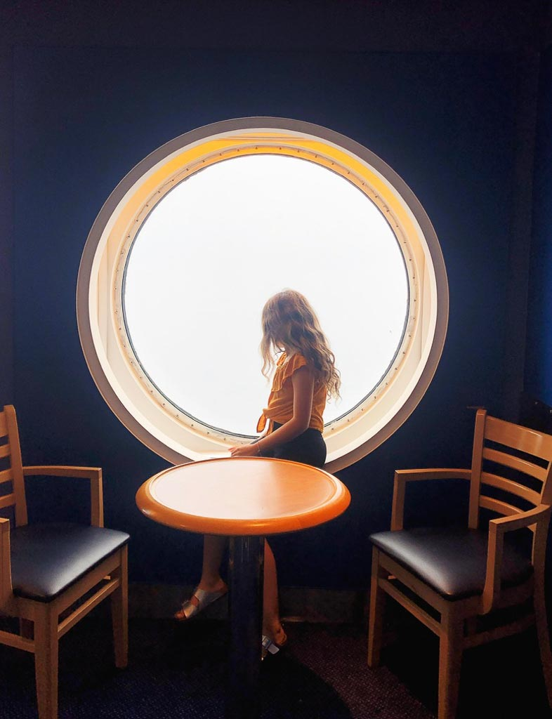 young girl in orange top looking out a round window on a ferry