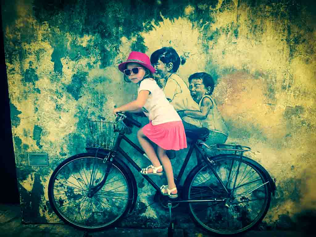 girl in pink hat pretending to ride a street art bicycle in penang