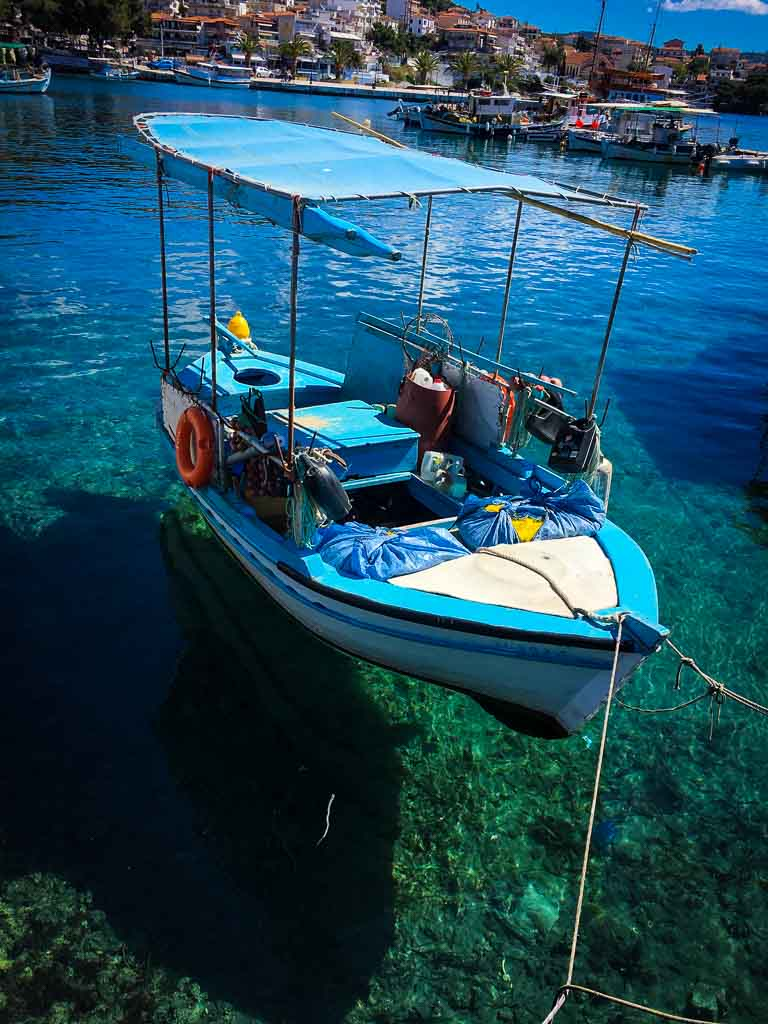tiny fishing boat with blue roof floating on crystal clear sea in rhodes