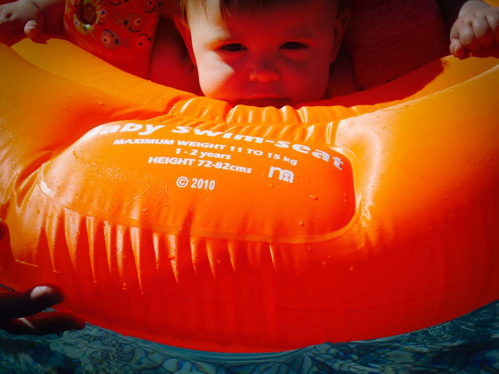 babys face pocking over a bright orange pool ring on a uk staycation