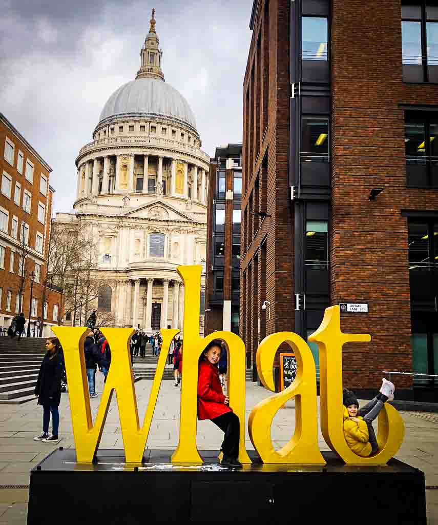 "huge word ""what"" with two girls sat in the letters in front of st Pauls cathedral"