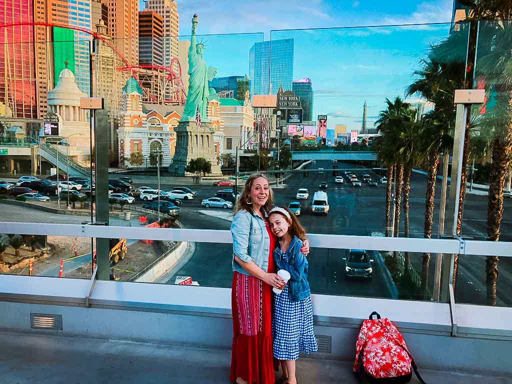 karen quinn and piper quinn on a bridge over the las vegas strip with new york new york hotel in the background
