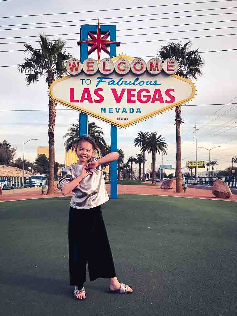 young girl in black trousers and silver top infront of the welcome to las vegas sign
