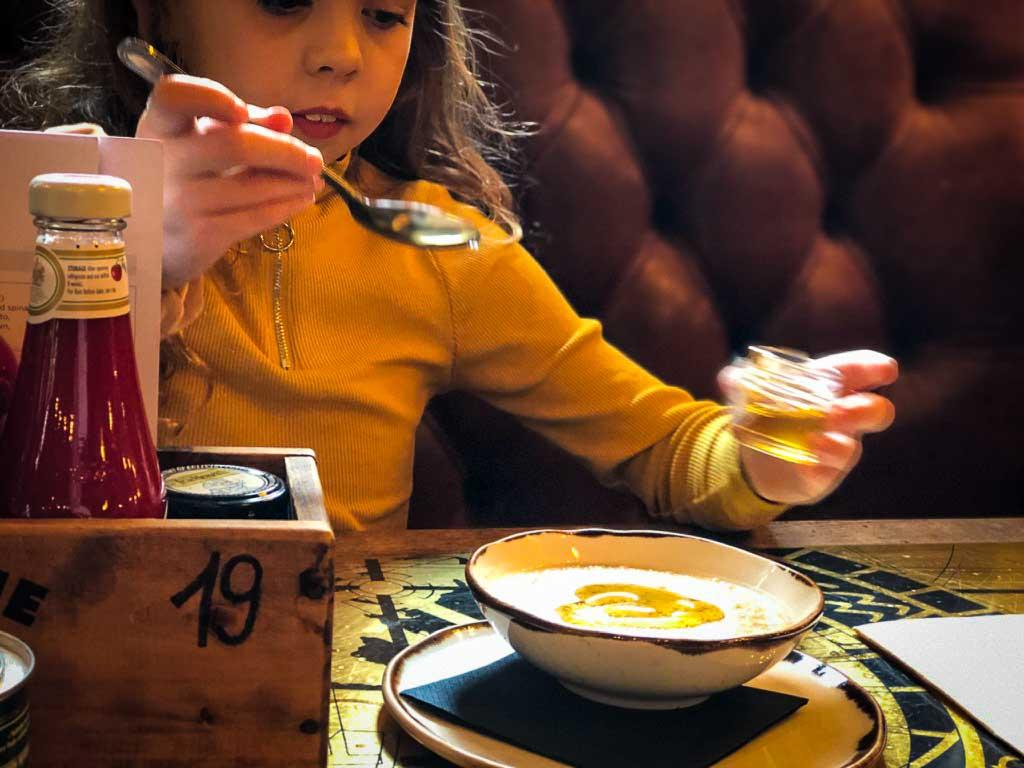piper quinn pouring honey on a bowl of porridge at a family restaurant in london
