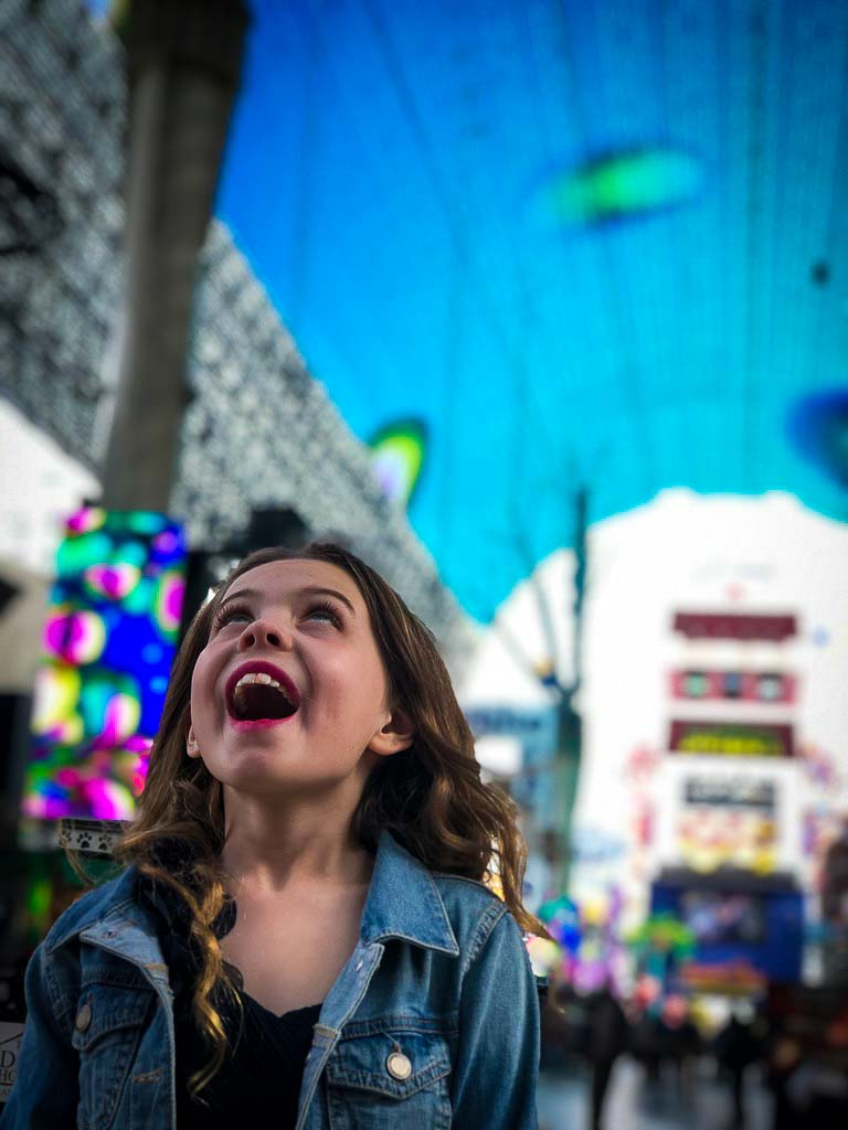 piper quinn looking up at the colourful canopy at the fremont street experience