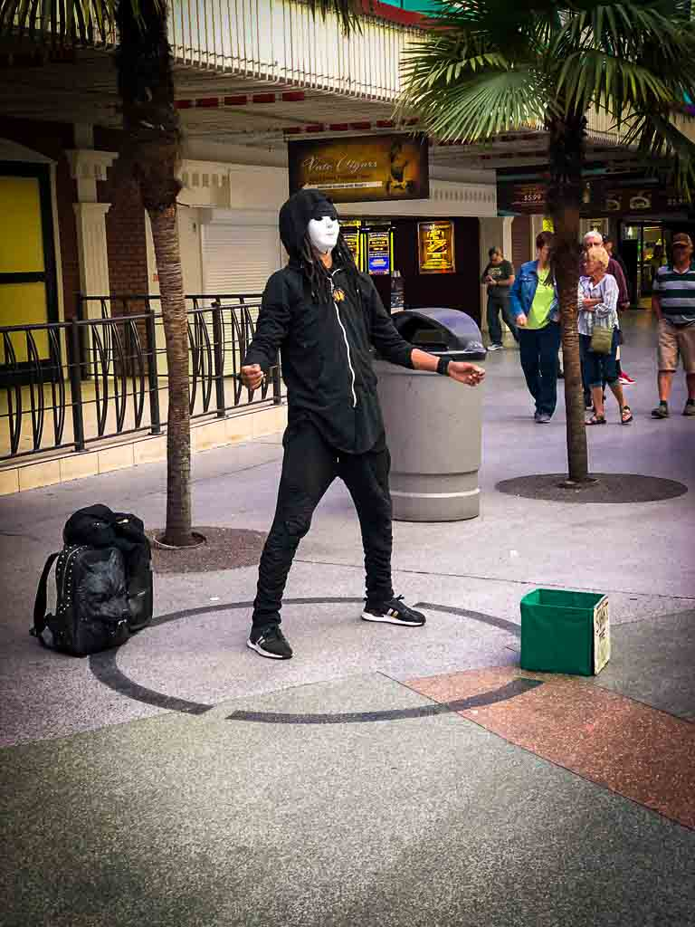 street performer dressed in black with a white mask at fremont street
