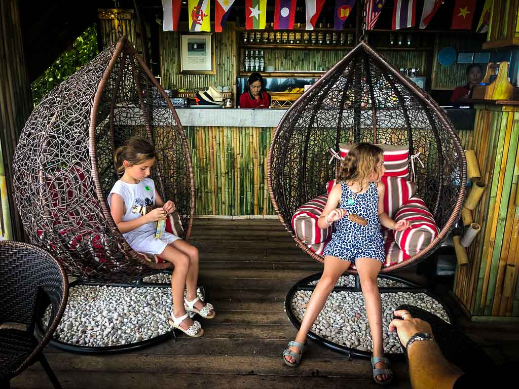 two girls sat in wood hanging chairs in a cafe