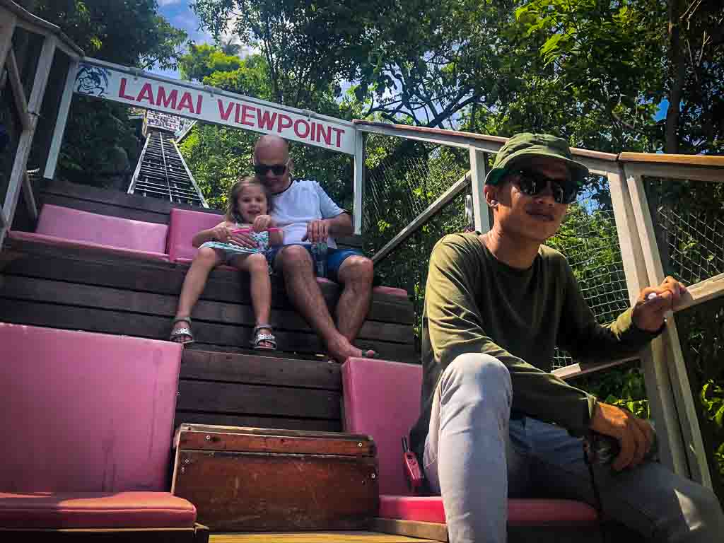 family sat at the top of a pink funicular car in koh samui