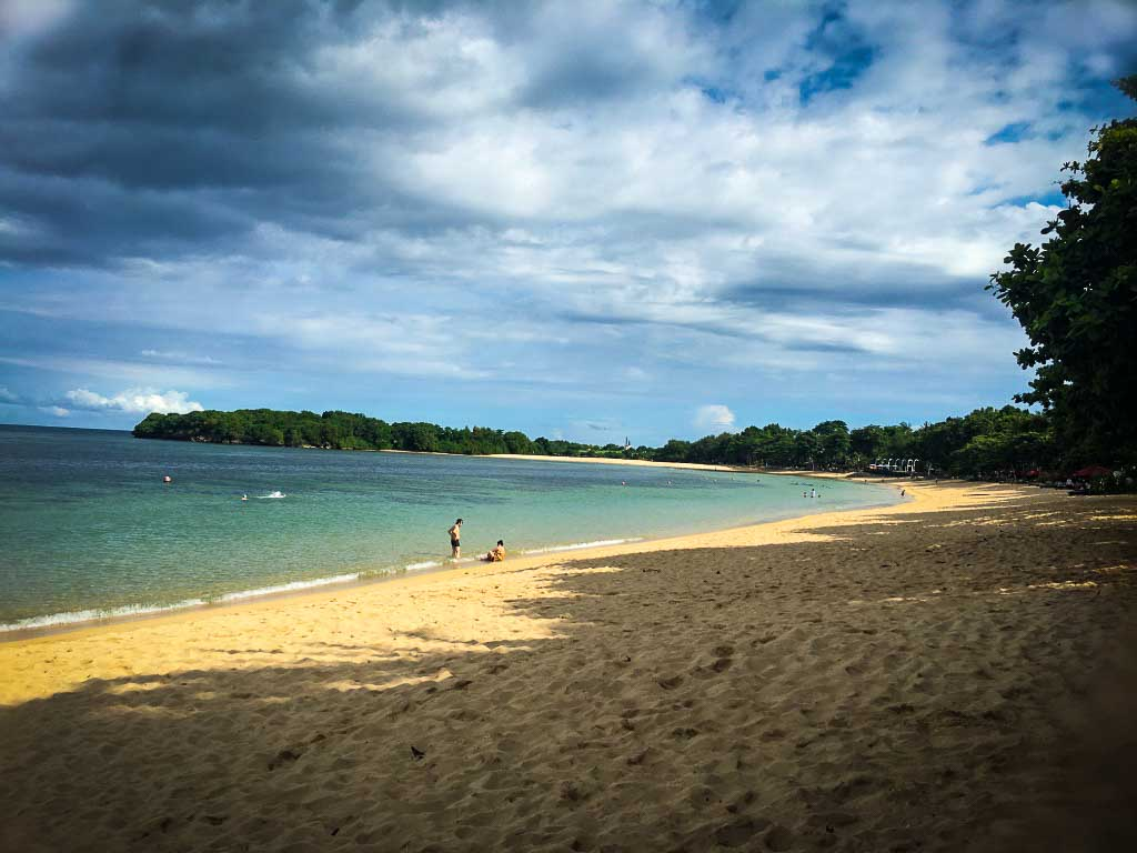 nusa dua beach in Bali, blue water and pale yellow sand