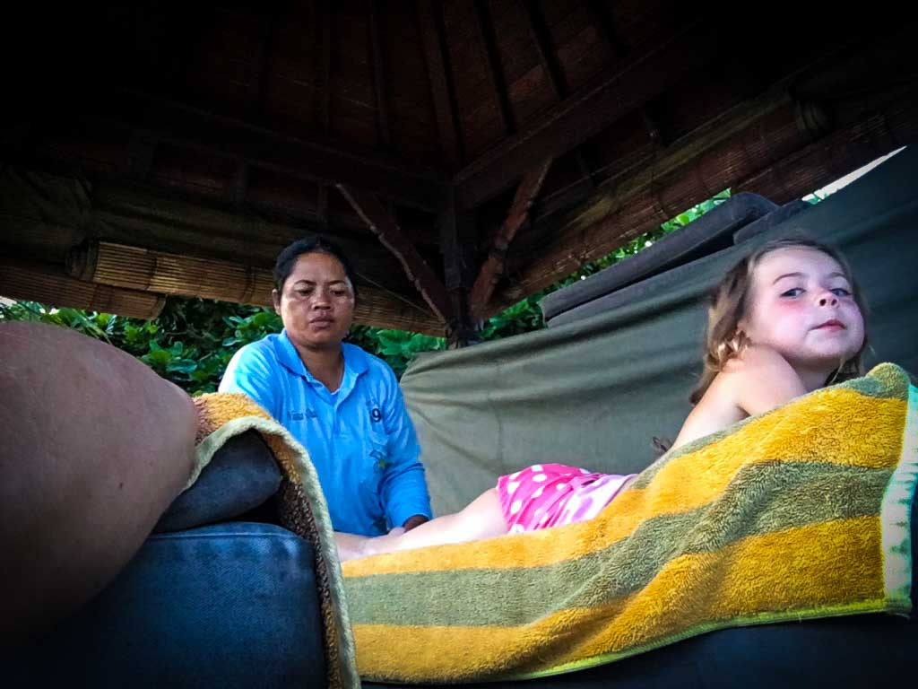 piper quinn getting a massage at a beach stand in Bali