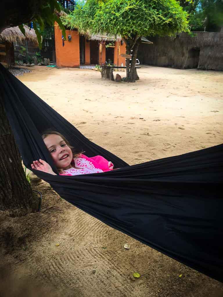 piper quinn in a pink dress hiding in a black hammock