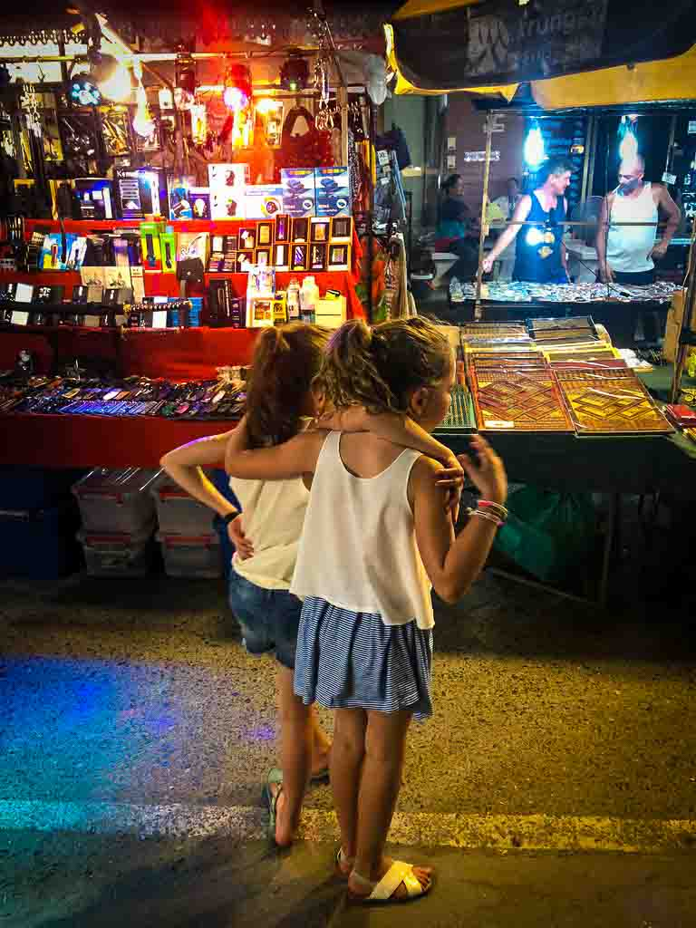 two ten year old girls in blue skirts and white tops with their arms around each other in a thai night market