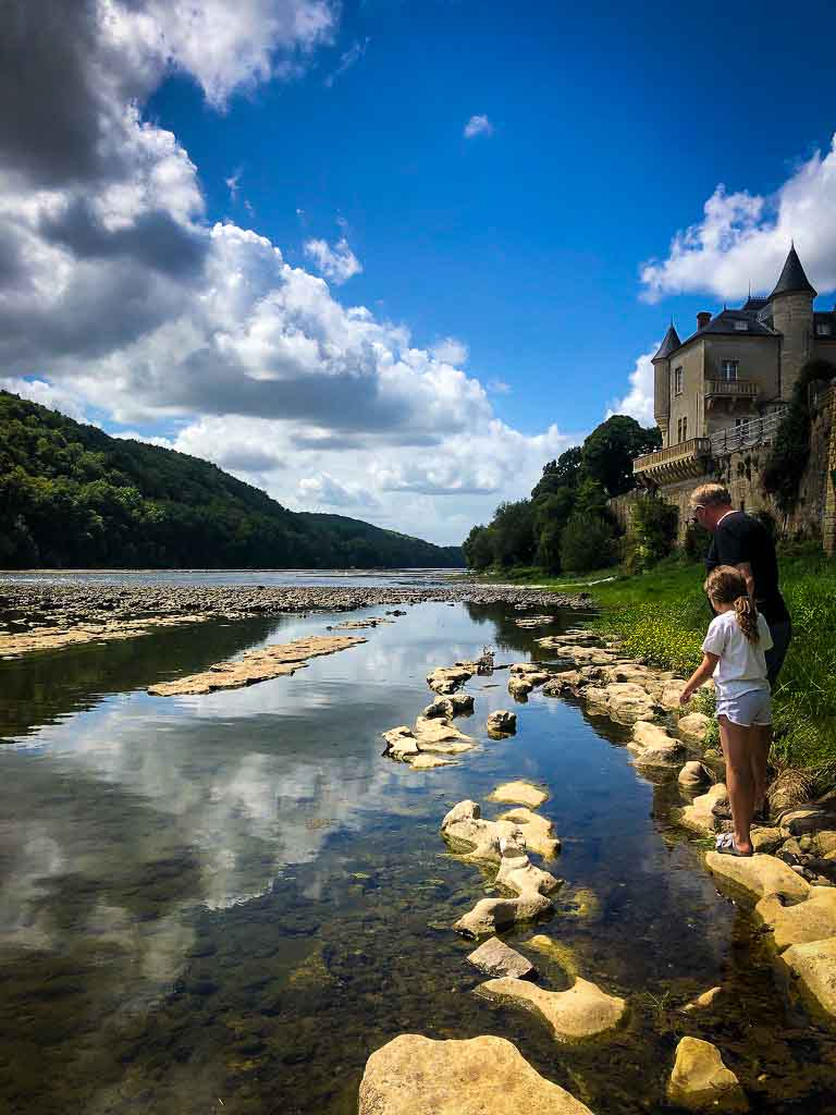 girl and father standing on the edge of a river in the dordogne region of france