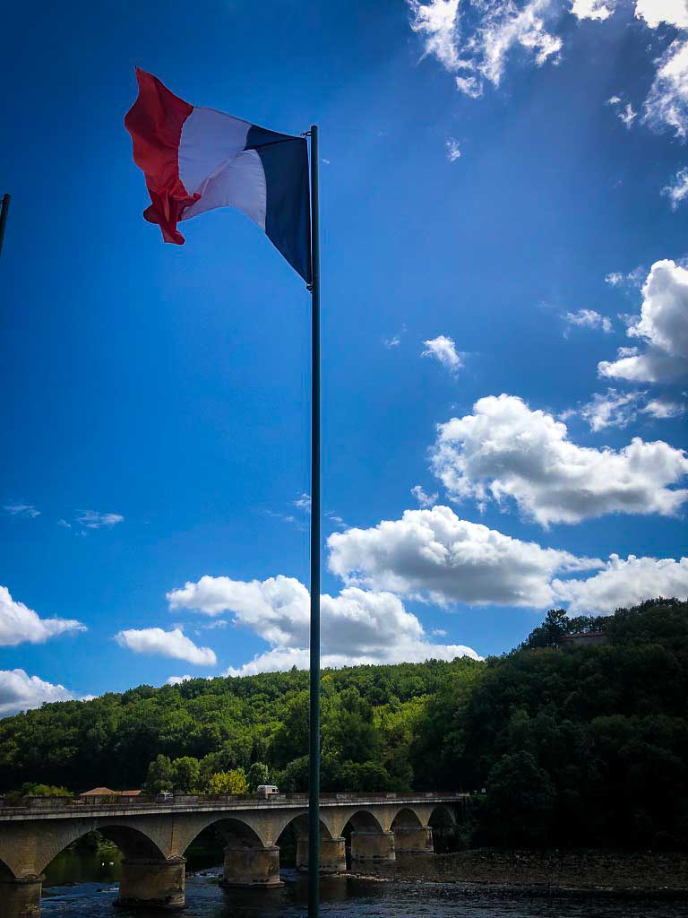 french flag against a blue sky with a few clouds