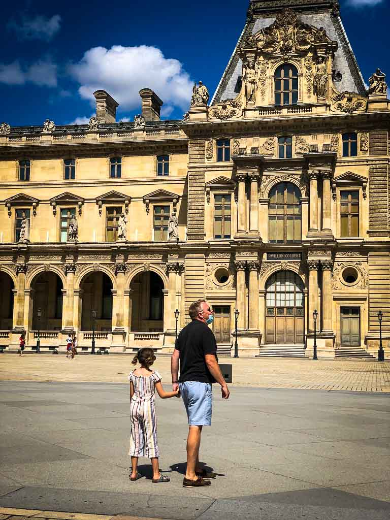 girl holding hands with her dad exploring the Louvre area of paris