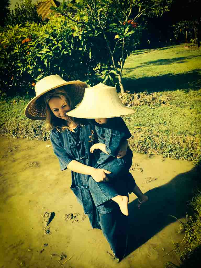 mother in traditional thai farmer clothes holding her daughter is a rice field in Chang Mai