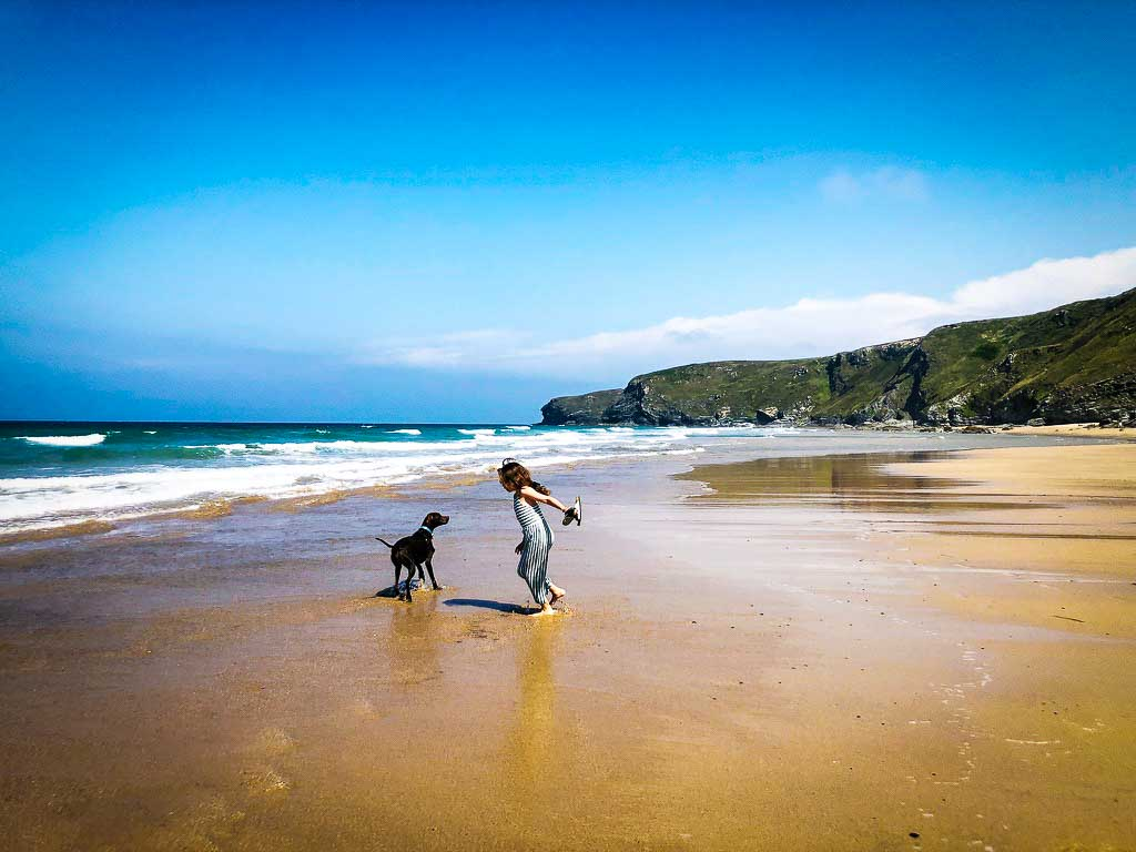girl and dog playing on a beach in cornwall