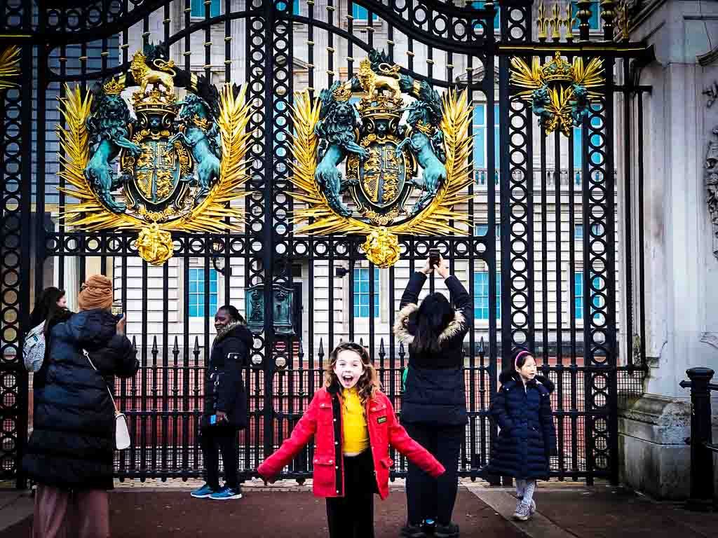 piper quinn outside buckingham palace gates. She is wearing a red coat and looks very excited